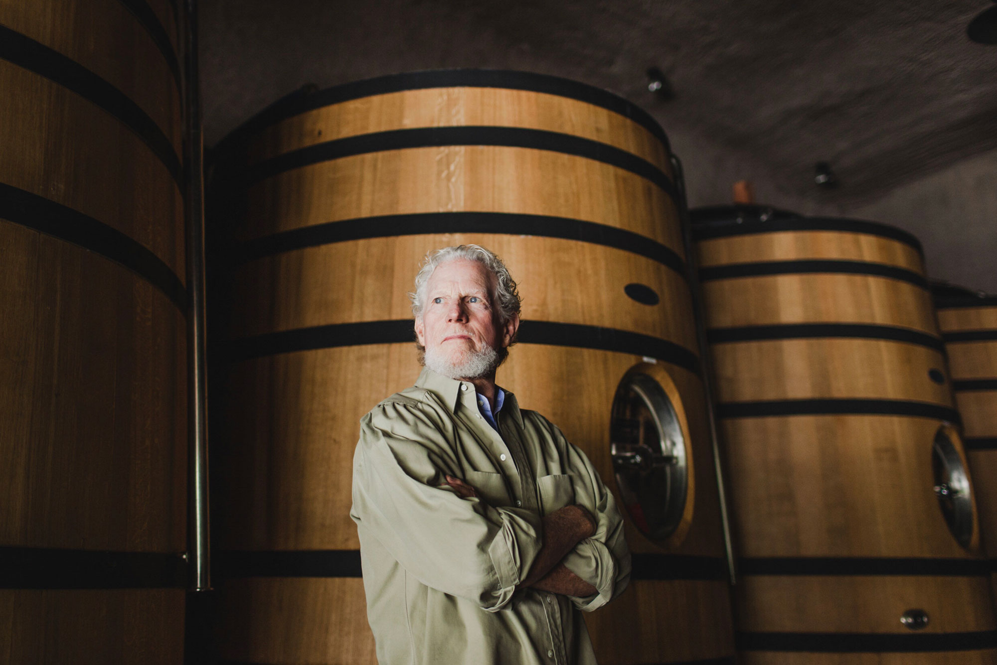 Winemaker with wooden wine tanks